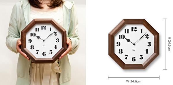 八角の時計を女性が持っている画像