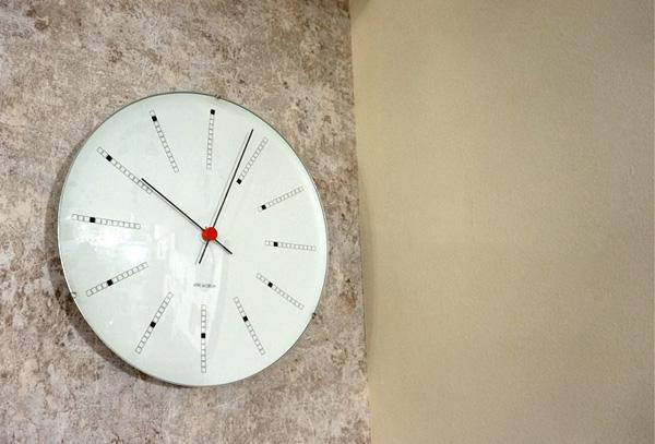 時計を石の壁に掛けてある画像