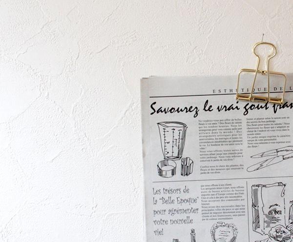クリップで紙を挟んで壁にかけている画像