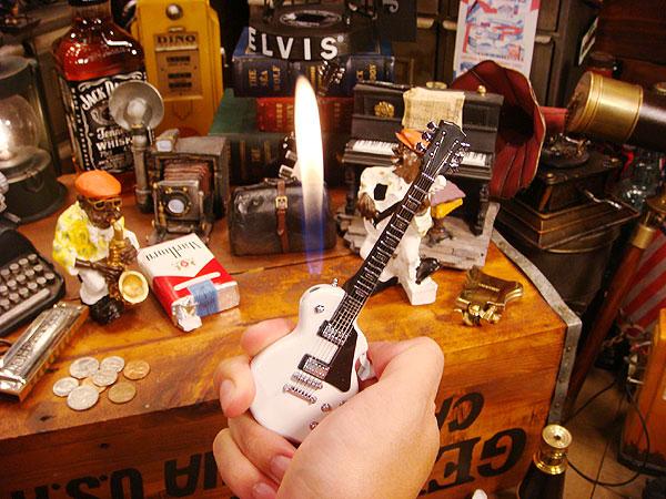 ギター型ライターを手に持って使っている画像