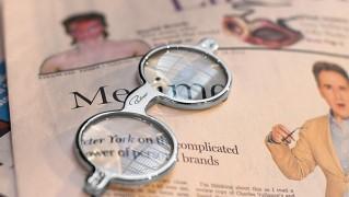 グラスルーペを新聞の上に置いた画像
