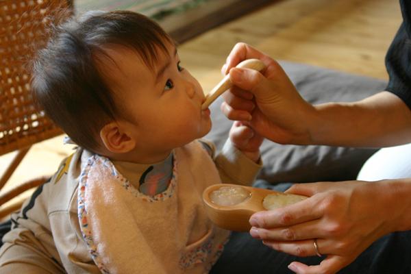 赤ちゃんに離乳食を食べさせている画像