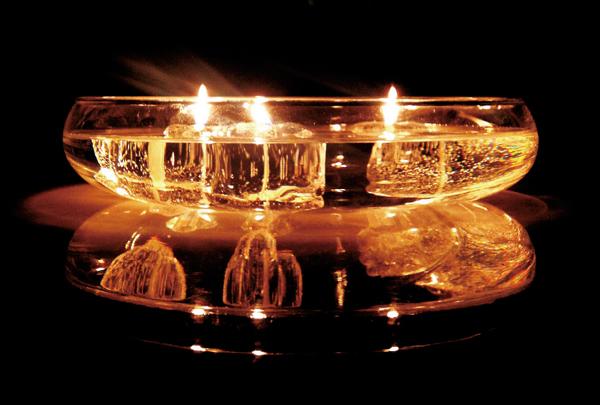 3つのBURNICEに火を灯してガラスの器に浮かべている画像