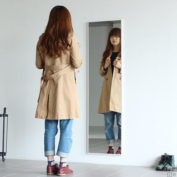 女性が姿見で服装のチェックをしている画像